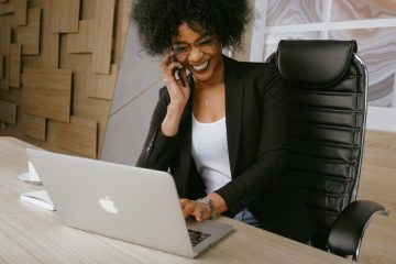 Happy woman talking on the phone and sitting at a desk with her laptop